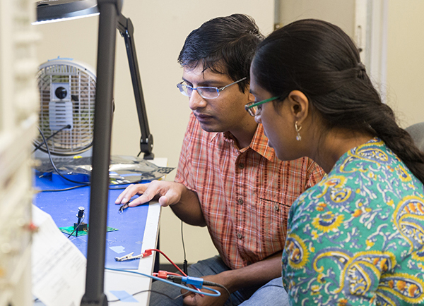 Photo of a professor with a female graduate student in the analog-mixed signal lab