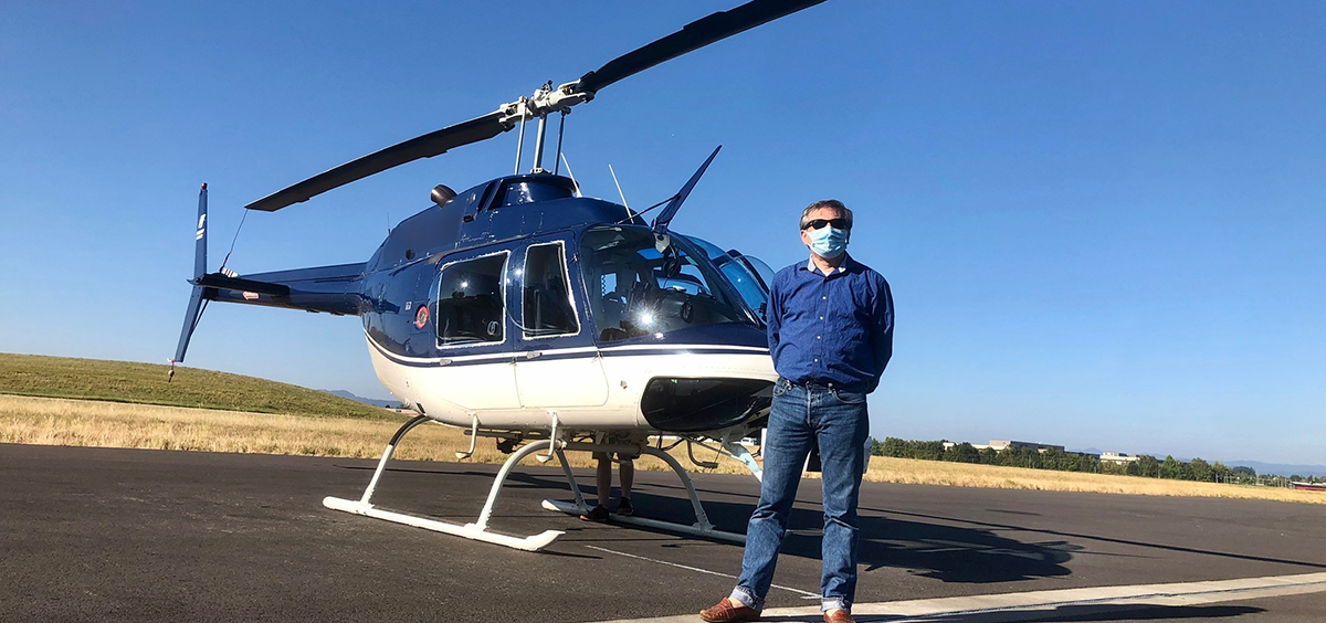 Photo of Carlo Tiana in front of a helicopter