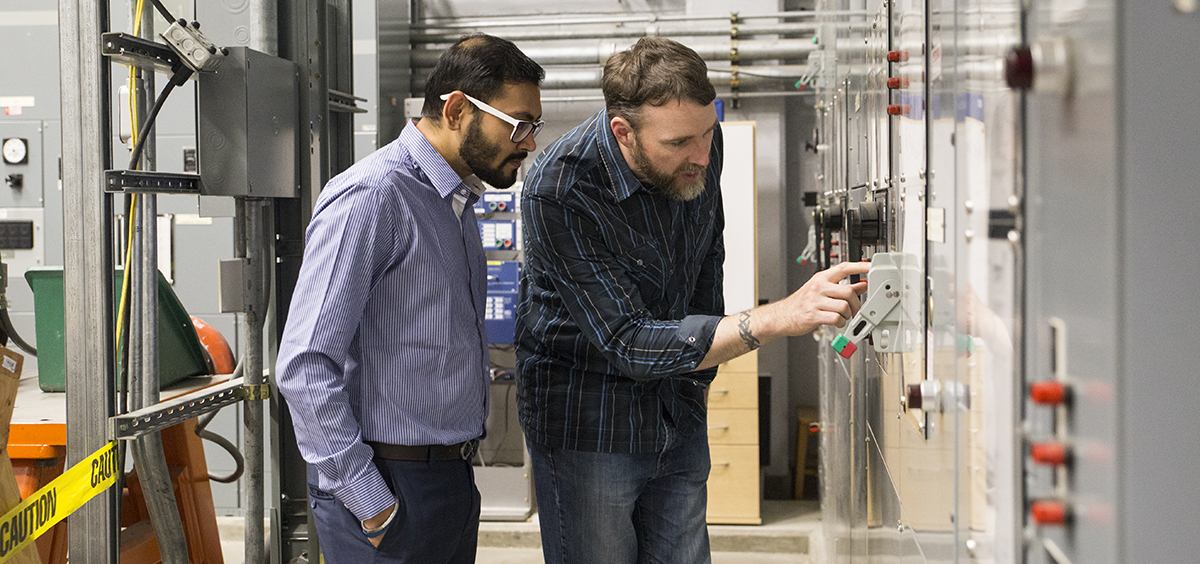 Photo of male student and male professor inspecting power controls