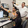 Photo of two graduate students and a Tektronix representative in the lab.