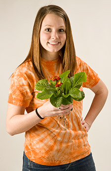 Photo of a college student holding a plant