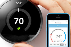 Photo of a Nest thermometer and mobile phone