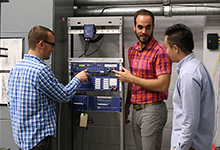 Photo of a professor and students looking at synchrophaser